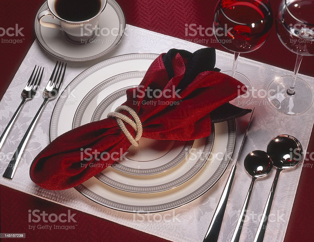 Complete place setting with ornate red napkin and tablecloth royalty-free stock photo