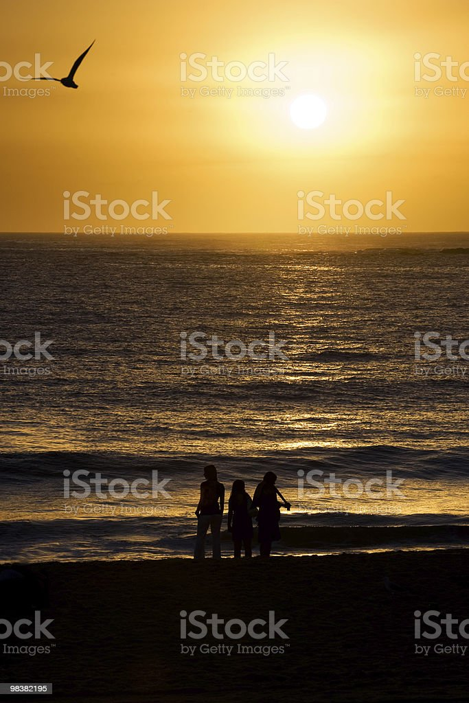 Completed sunrise over ocean and beach, with people silhouette royalty-free stock photo