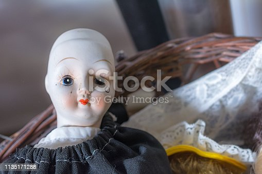 Bald vintage doll with tear and heart shaped mouth and thin eyebrows on yard sale