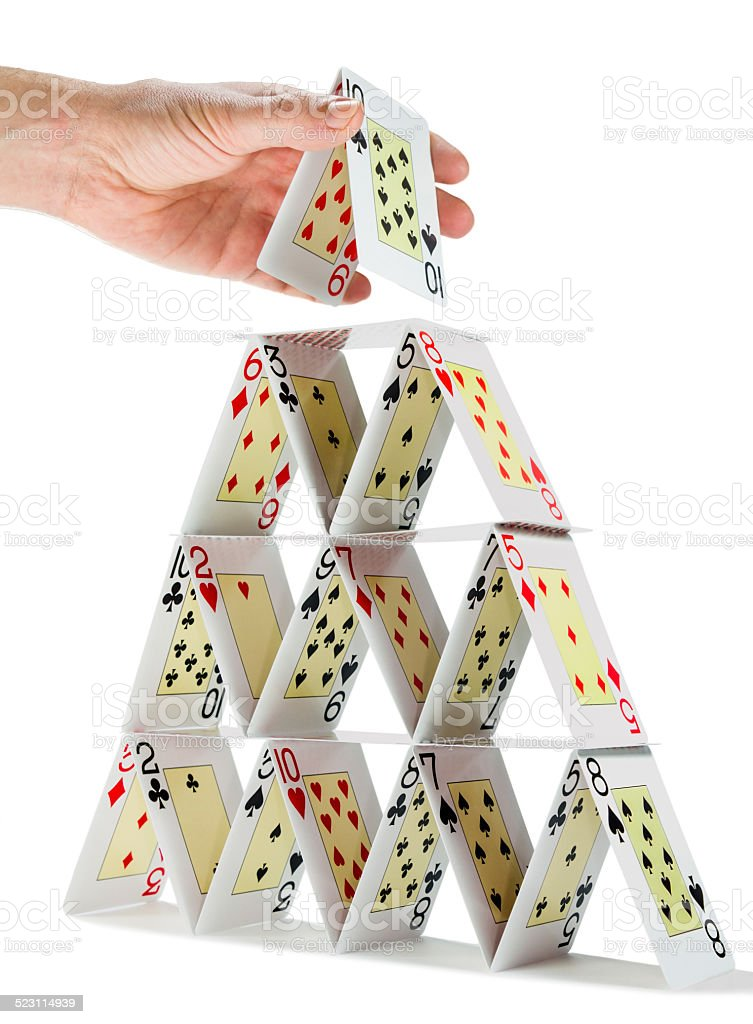 Completing a house of cards isolated on white stock photo