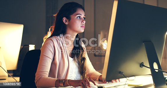 Cropped shot of a beautiful young woman working at night in a modern office