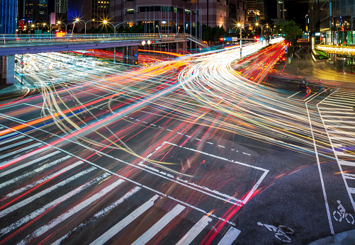 Multiple vehicle light trails illuminating the busy streets of downtown Taipei in a long exposure at night during rush hour.