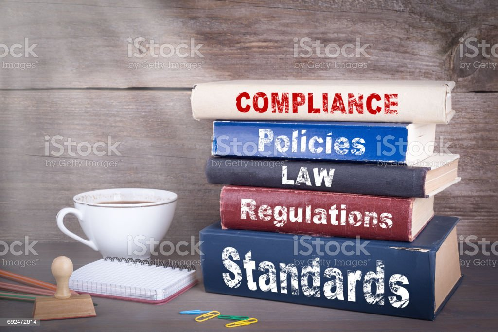 Compliance concept. Stack of books on wooden desk stock photo