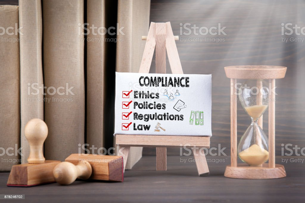 Compliance concept with icons. Sandglass, hourglass or egg timer on wooden table showing the last second or last minute or time out stock photo