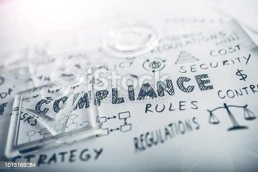 Transparent check mark over compliance related icons and words handwritten on white papers