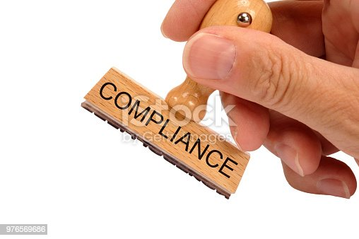 istock compliance printed on rubber stamp in hand 976569686