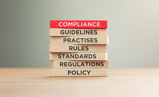 Compliance related words written wood blocks sitting on a wood surface in front of a defocused background. Compliance concept.