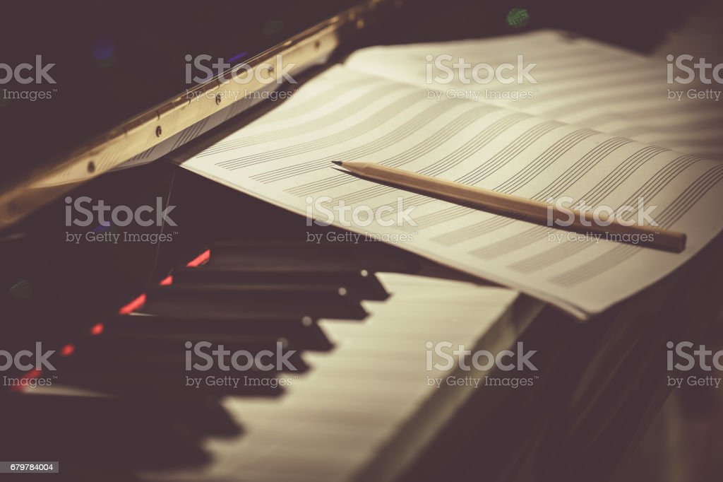 Compose Concept. Pencil and sheet music on the piano keyboard stock photo