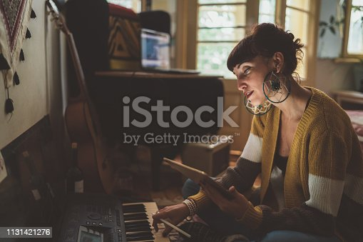 Young woman sitting on floor and creating new music