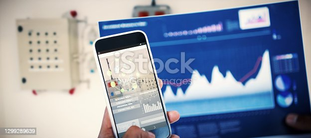 Cropped image of hand holding 3D mobile phone and graph against workshop