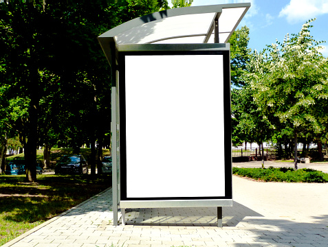 composite raster image of bus shelter at a bus stop of transparent clear glass and aluminum frame structure in green street setting with trees and street in the background. milky white poster ad and banner display glass. white light box. copy space.