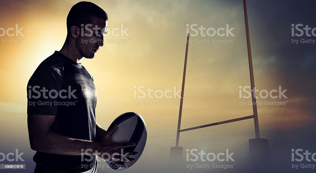 Composite image of calm rugby player thinking while holding ball stock photo