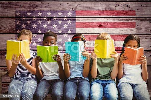 istock Composite image of children reading books at park 486253220