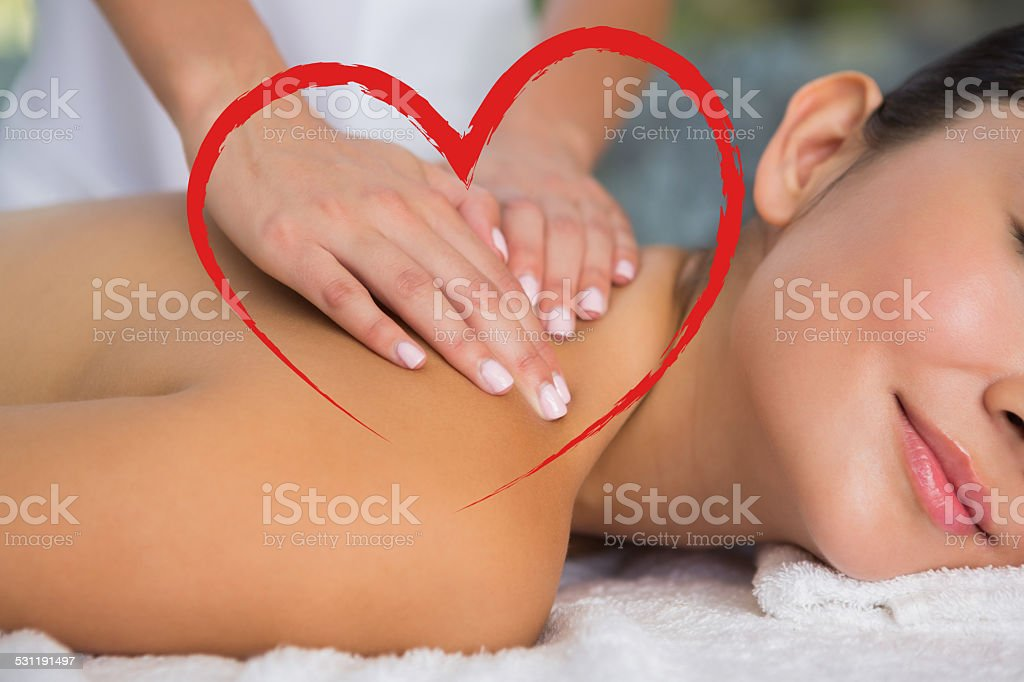 Composite image of content brunette getting a back massage stock photo