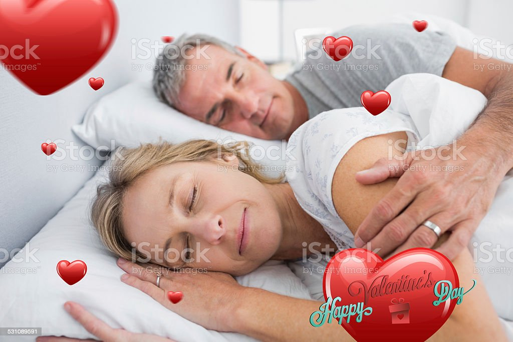 Composite image of couple sleeping and spooning in bed stock photo