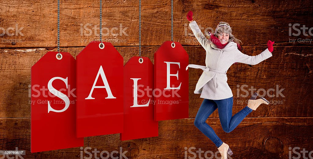 Composite image of happy blonde in winter clothes posing stock photo