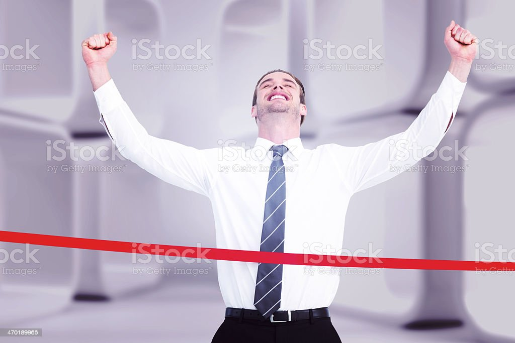 Composite image of happy businessman crossing the finish line stock photo