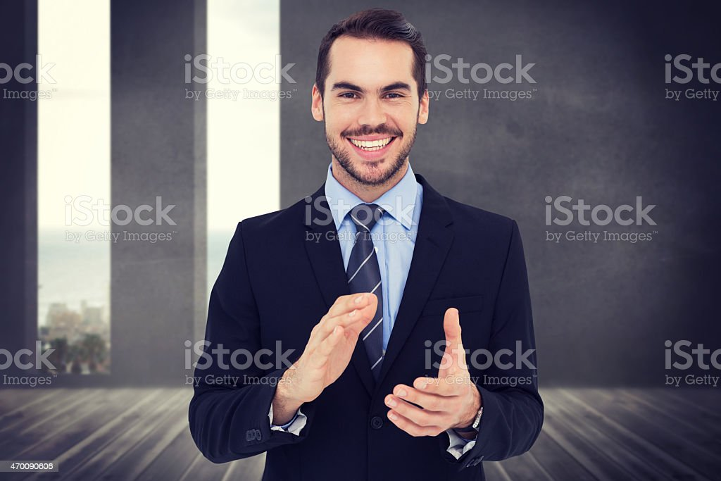 Composite image of happy businessman standing and applauding stock photo