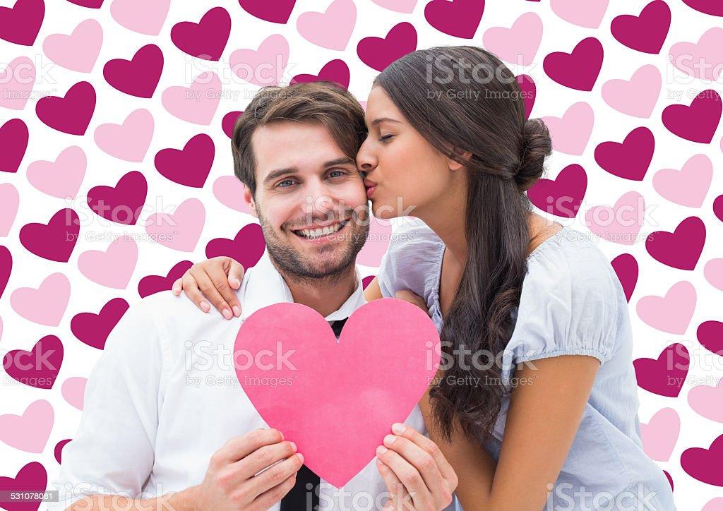 Composite image of pretty brunette giving boyfriend a kiss stock photo