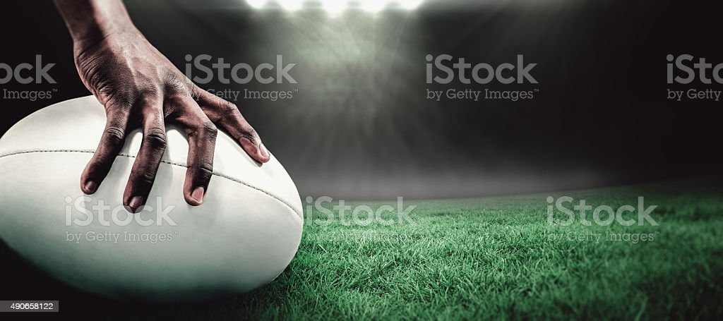 Cropped image of sportsman holding rugby ball against rugby stadium