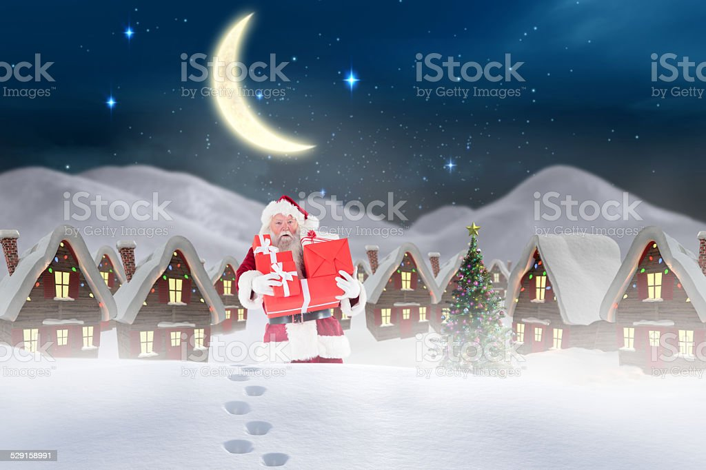 Composite image of santa carrying gifts in the snow stock photo