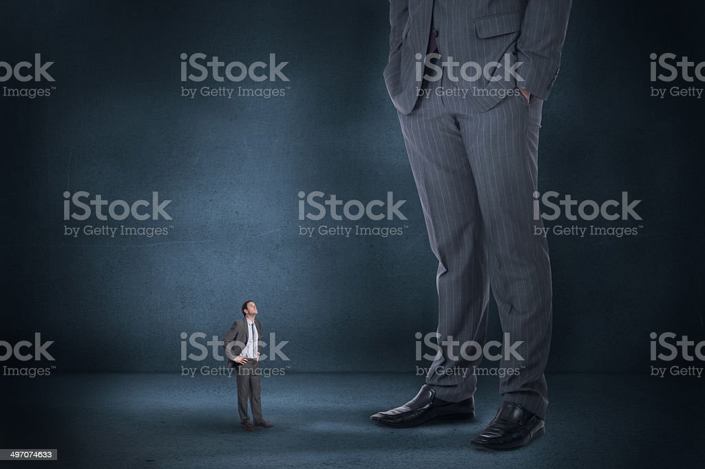 Composite image of serious businessman with hands on hips and stock photo
