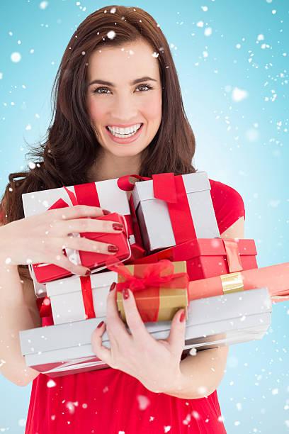 composite-bild der lächelnde brunette holding viele geschenke - wickelkleid lang stock-fotos und bilder