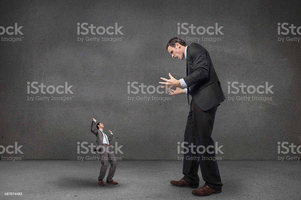Composite image of stressed businessman gesturing at tiny busine stock photo