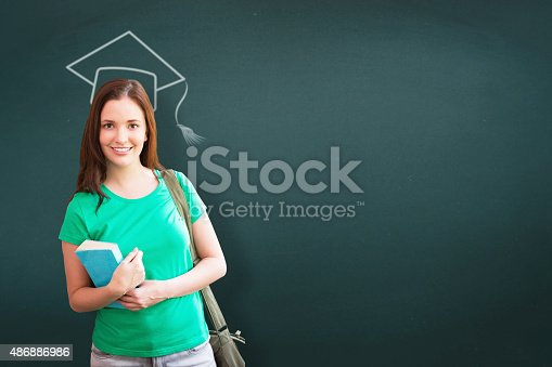 istock Composite image of student smiling at camera in library 486886986