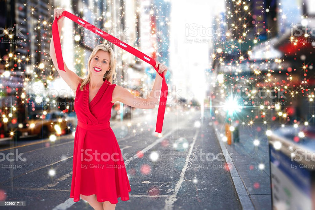 Composite image of stylish blonde in red dress holding scarf stock photo