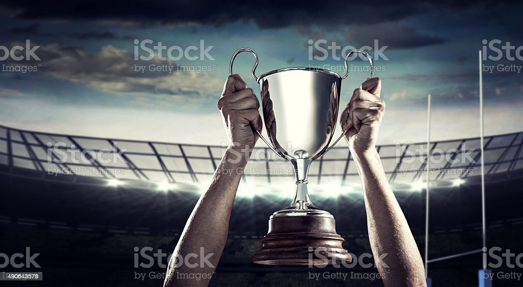 Composite image of successful rugby player holding trophy stock photo