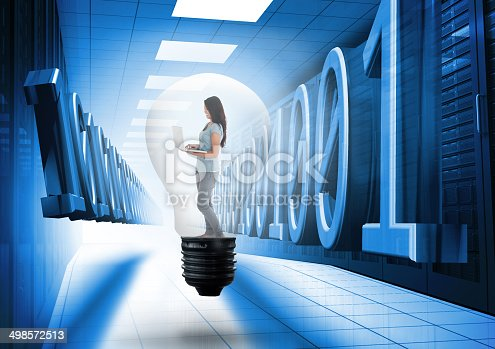511983606istockphoto Composite image of woman holding laptop in light bulb 498572513