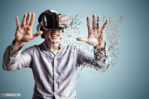 1003539592 istock photo Composite image of young man using black virtual reality glasses by table 1199958738
