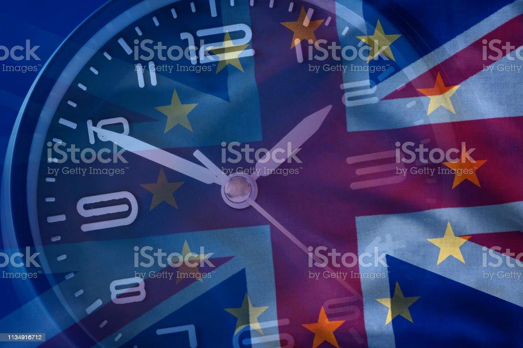 Zusammenhaltung von EU und britischer Flagge mit einer Uhr – Foto