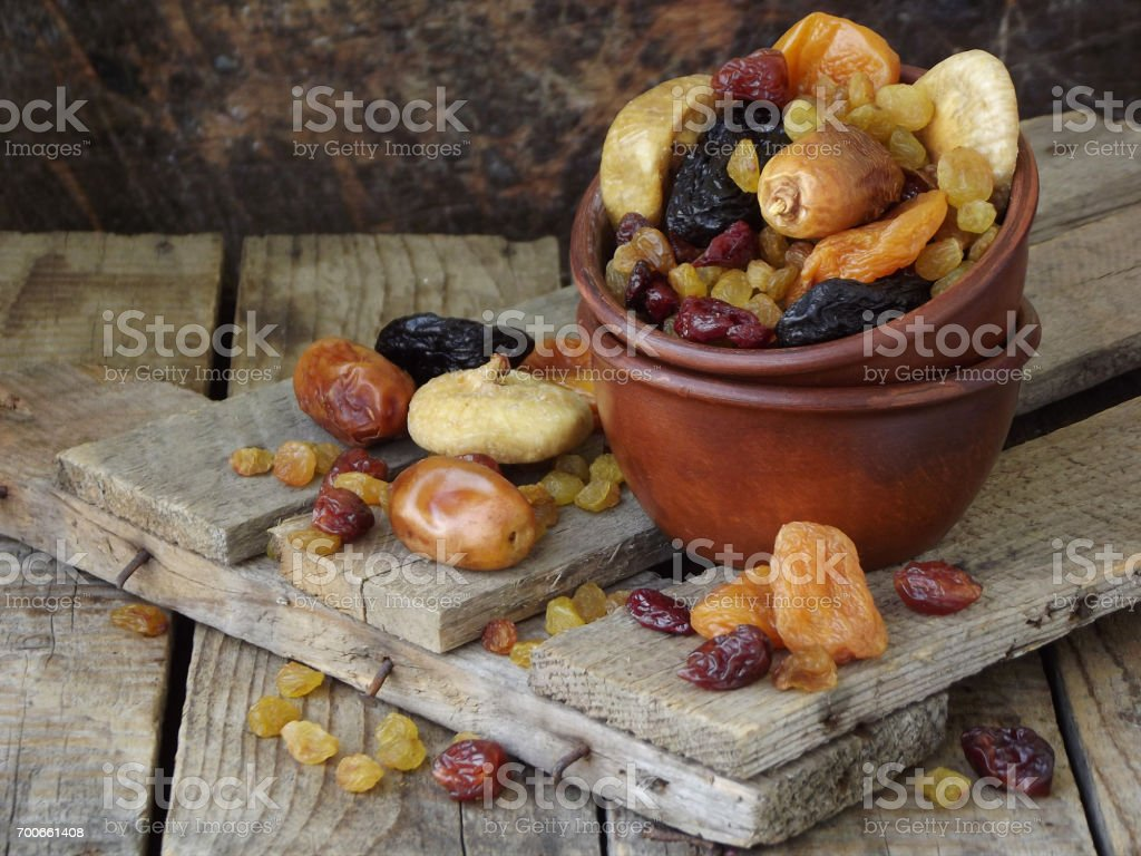 A composition from different varieties of dried fruits on a wooden background - dates, figs, apricots, prunes, raisins, cranberries. Healty food. stock photo