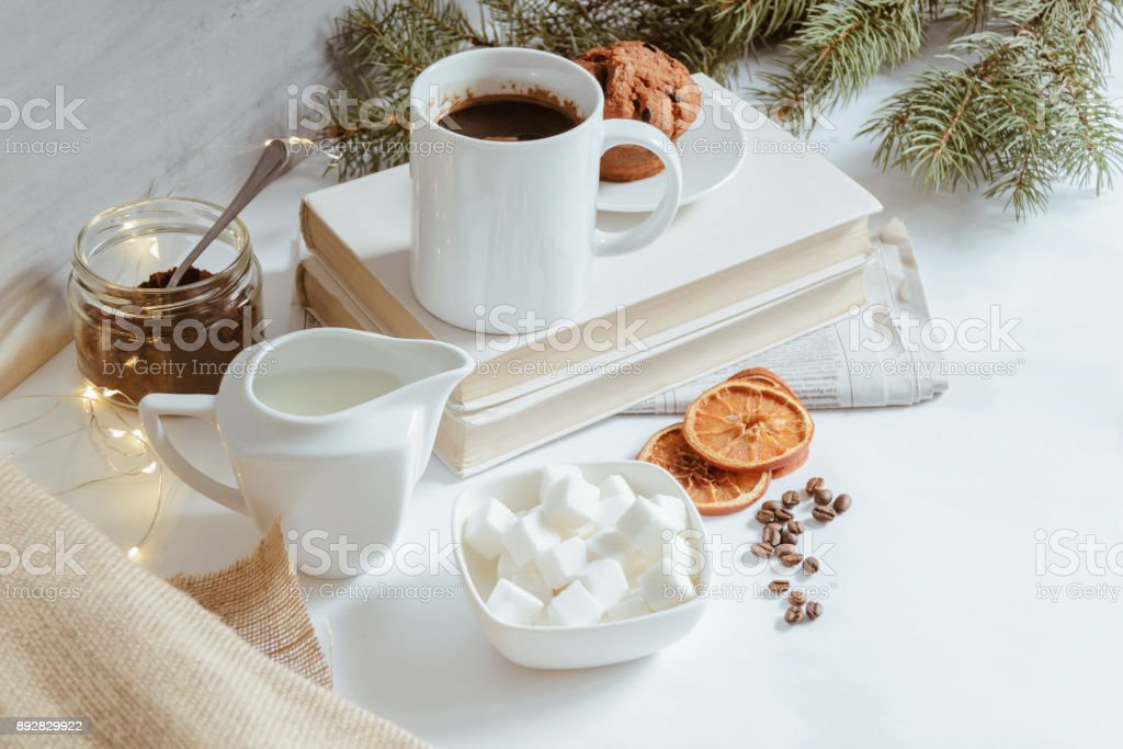 Composition of a fresh coffee, dried lemons, milk, and sugar cubes stock photo
