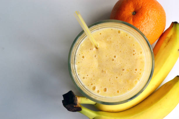 A composition of bananas and orange and a glass with smoothies stock photo