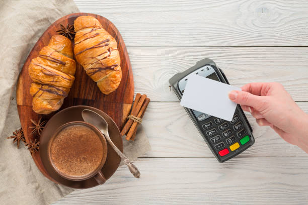 composition of coffee and croissants with bank payment terminal on a wooden background - paying with card contactless imagens e fotografias de stock