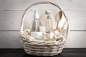 Composition of cosmetic bottles and soap in basket, on white wooden background