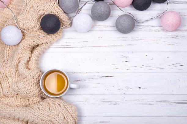 Zusammensetzung der Tasse Tee und Beige kariert, dekoriert mit Baumwolle Kugeln Licht Girlande auf weißem Hintergrund aus Holz. – Foto