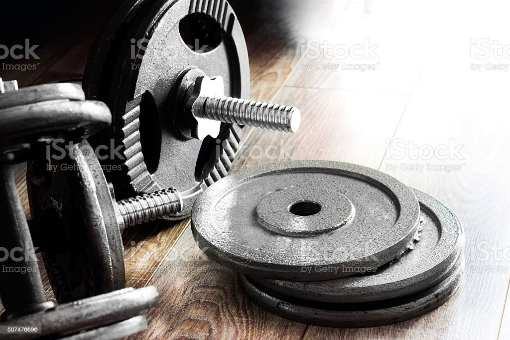 Composition of dumbbells and barbells on the wooden background stock photo