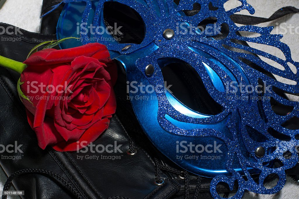 Composition of erotic black corset, red rose and blue mask stock photo