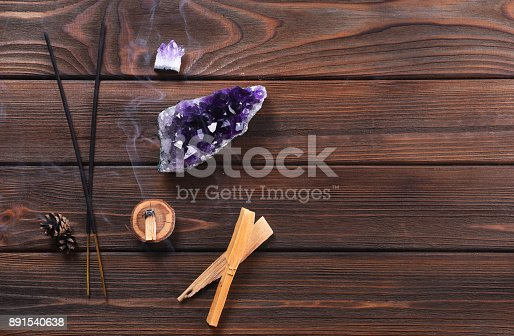 istock Composition of esoteric objects used for healing, meditation, relaxation and purifying. Amethyst stones, palo santo wood, Aromatic sticks on dark background. 891540638