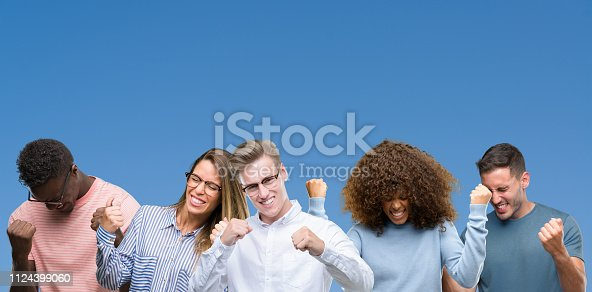 istock Composition of group of friends over blue blackground very happy and excited doing winner gesture with arms raised, smiling and screaming for success. Celebration concept. 1124399060
