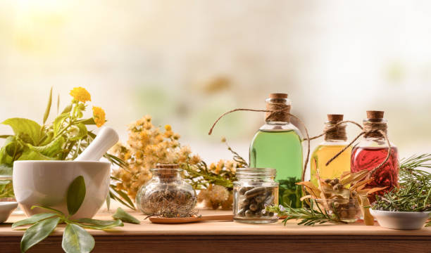 Composition of natural alternative medicine with capsules essence and plants Composition of natural alternative medicine with capsules, essence and plants on wooden table in rustic kitchen. Front view. Horizontal composition. herbal medicine stock pictures, royalty-free photos & images
