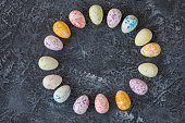 Composition of Easter eggs on dark natural stone background with copy space