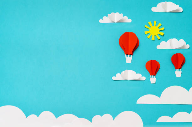 Composition of paper cut hot air balloons, clouds, and sun on bright sky. Creative concept for banner/landing/background designs. stock photo