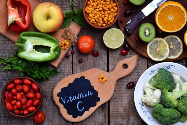 samenstelling van producten met ascorbinezuur, vitamine c - citrus, bloemkool, broccoli, paprika, kiwi, hondsroos, tomaten, appel, bessen, zee duindoorn. bovenaanzicht. flat lag. - vitamine c stockfoto's en -beelden