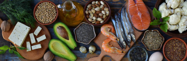 Composition of products containing unsaturated fatty acids Omega 3 - fish, nuts, tofu, avocado, egg, soybeans, flax, pumpkin seeds, chia, hemp, cauliflower, dill, vegetable oil. Top view. Healthy food stock photo
