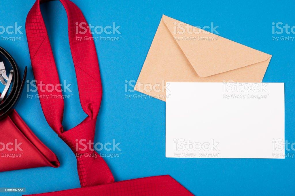 Composition of red neck tie, pocket square, belt, craft envelope and...